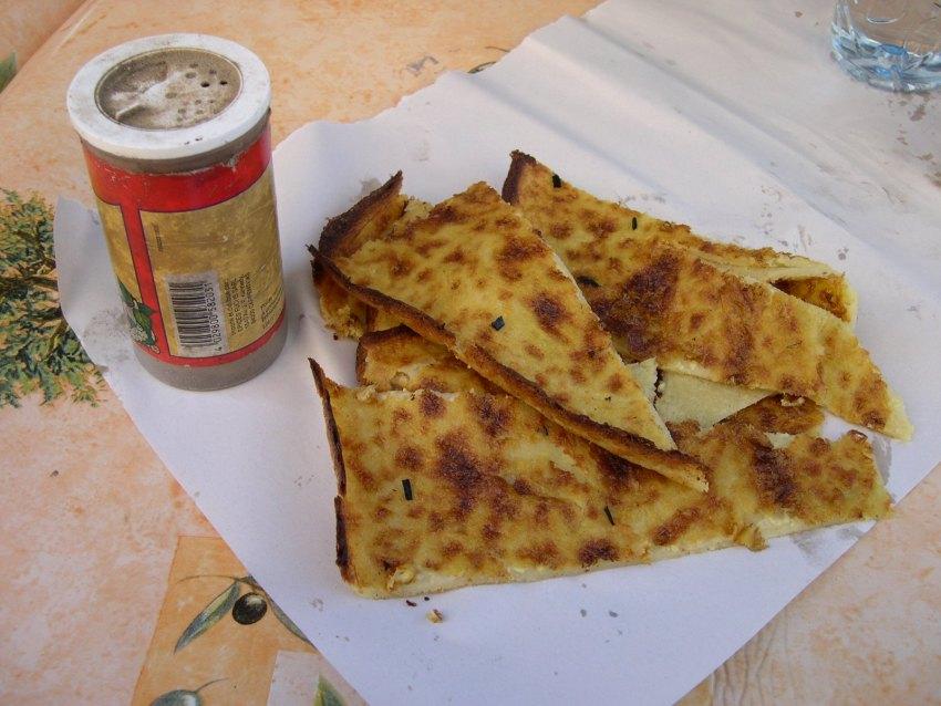 Ενα πιάτο με ψωμί socca όπως το σερβίρουν ως street food στη Νίκαια (Φωτό Wikipedia)